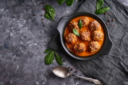 homemade meatballs with tomato sauce and spinach in a plate on a dark background Top view Copyspace