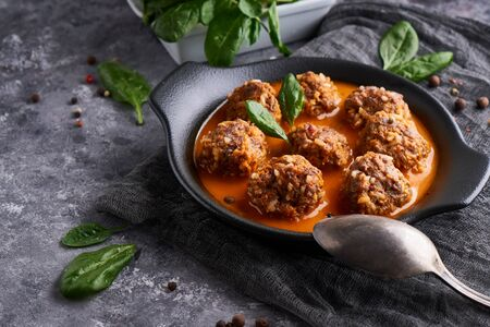 Tasty homemade meatballs with tomato sauce and spinach served in a plate on a dark stone table Copy space 스톡 콘텐츠