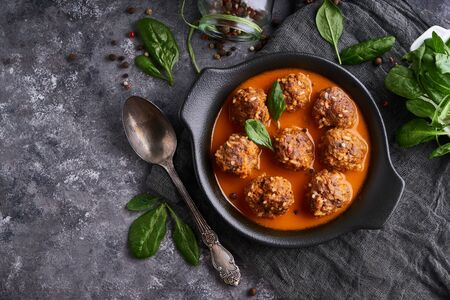 homemade meatballs with tomato sauce and spinach and spicy in a plate on a dark background Top view 스톡 콘텐츠