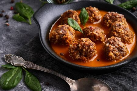 Appetizing homemade meatballs with tomato sauce and spinach served in a plate on a dark stone table Close up
