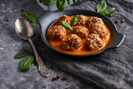Tasty homemade meatballs with tomato sauce and spinach in a plate on a dark background Close up
