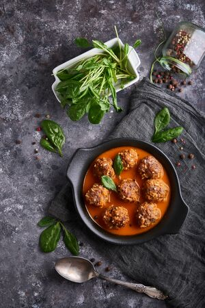 Tasty homemade meatballs with tomato sauce and spinach served in a plate on a dark stone table Vertical