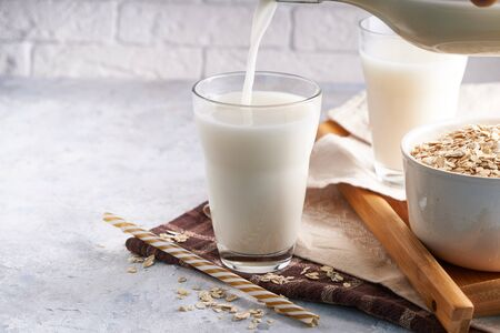 Healthy alternative milk. Homemade oak milk in glass and bottle on light table Lactose free Copy space