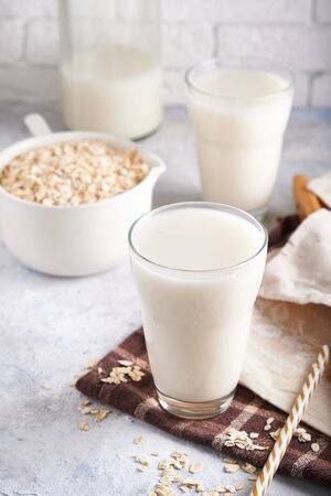 Healthy alternative milk. Homemade oak milk in glass and bottle on light table Lactose free Vertical 스톡 콘텐츠