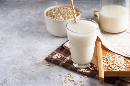 Healthy alternative milk. Homemade oak milk in glass and bottle on light table Lactose free