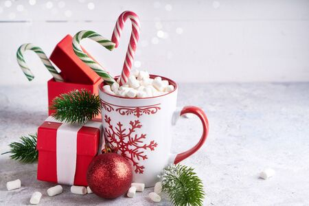Christmas cup with sugar cocoa marshmallows , gift box and candy . Fir branches, christmas gift box on light background Copy space Stock Photo