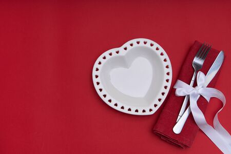 Valentines day concept. White plate in the shape of a heart on red background Copy space