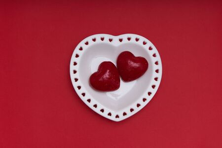 Mockup Valentines day. White plate in the shape of a heart with red candles on red background Copy space