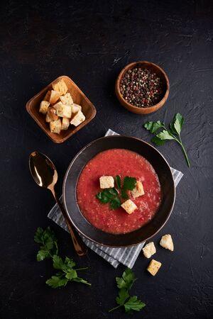 Soupe aux tomates espagnole traditionnelle Gaspacho aux épices dans un bol noir sur fond de pierre sombre Copiez l'espace vertical