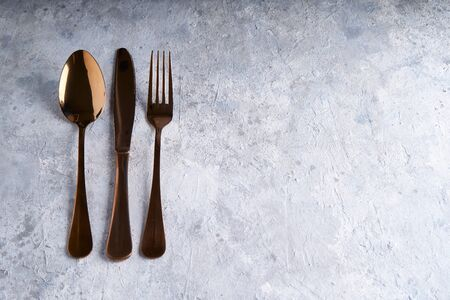 Bronze spoon, knife, fork on a light stone table Copy space Top view