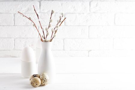 Easter concept White vase with willow branch , white egg, quail eggs and cups on a white table Copy space