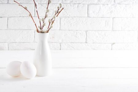 Easter concept White vase with willow branch and cups on a white table Copy space