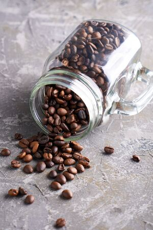 Coffee beans in a glass jar on a gray table Vertical Copy space