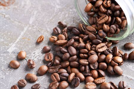Coffee beans in a glass jar on a gray table Copy space