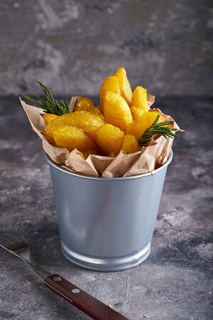 Fried potatoes country style. Barbecue potatoes. In a metallic bowl on a gray background Copy space