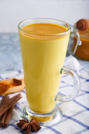 Turmeric milk. Cooked golden milk latte in a glass Close up