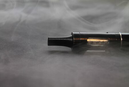electronic cigarette vaporizer on a gray background in smoke close up Stock Photo