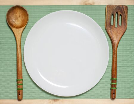 empty plate with wooden spoon and paddle on green background