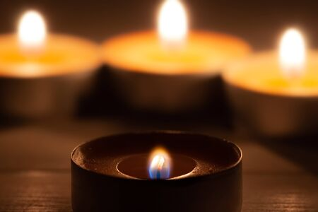 Three burning aroma candles and one burning low infront with wooden background macro