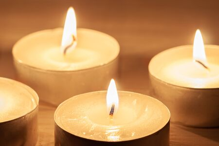 Several burning candles with wooden background macro