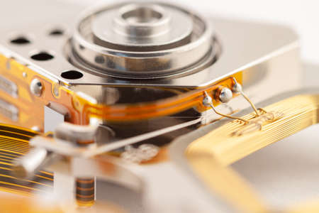 Hard drive detail with shiny metal and golden color parts on light background macro