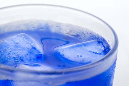 Bright glass refreshing beverage with melting ice cubes in blue alcohol syrop and condensation on its wall isolated white background macro
