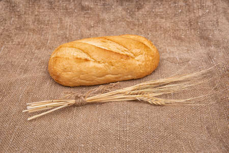 Loaf of rye bread or baguette on rustic wooden table with burlap close-up