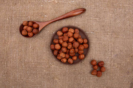 Nuts hazelnut in a wooden spoon and a brown earthenware plate on old burlap Stock fotó