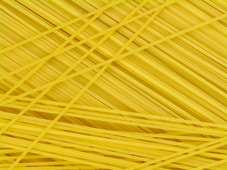 Spaghetti de pâtes italiennes jaunes non cuits situé de façon chaotique vue de dessus close-up