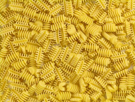 Uncooked yellow italian pasta marziani chaotically located texture top view close-up