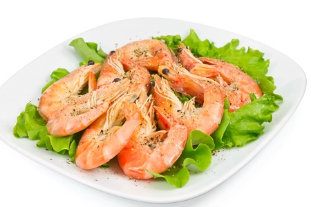 shrimp with peppers on a green salad on the plate