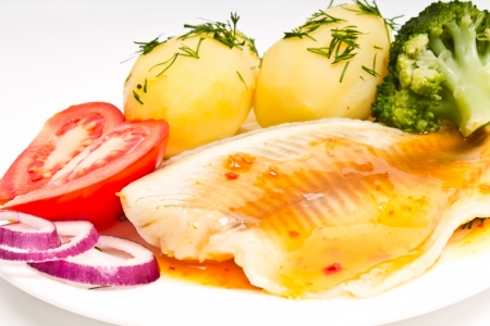 potatoes with dill, fish fillet, tomato and onion Фото со стока