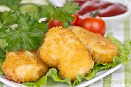 appetizing chicken nuggets with lettuce leaves, salad and tomatoes in the background Stock Photo