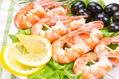 tiger prawns on a skewer with olives and lemon