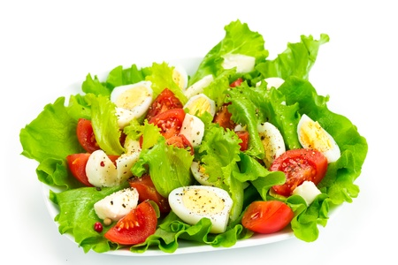 Tomato salad, quail eggs and mozzarella isolated on white background photo