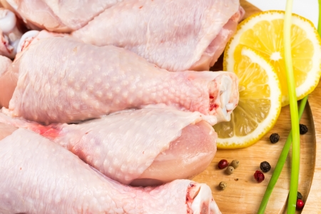 Raw chicken legs with lemon on a wooden board  photo