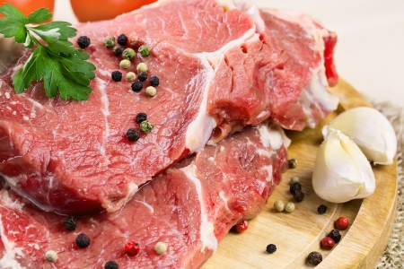 Raw beef steak with garlic and pepper