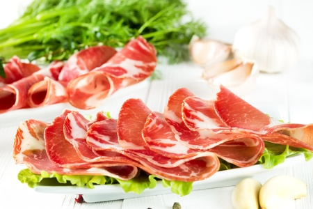 thinly: Thinly sliced ham on a narrow white plate