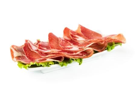 thinly: Thinly sliced ham on a white plate isolated on white background  Stock Photo