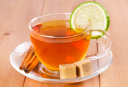 Tea in a glass cup with lime and cinnamon stick  photo