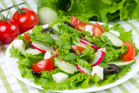 Salad with fresh vegetables and olives on a plate