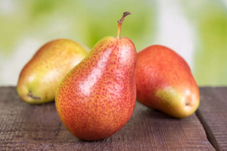 Three ripe pears on old wooden board photo