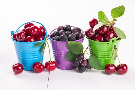 Cherries and blueberries in a bucket on a wooden board photo