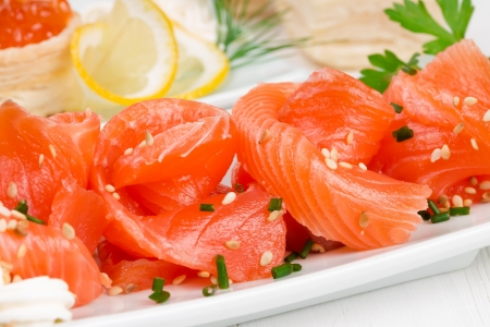 Sliced salmon with sesame seeds on a white plate photo