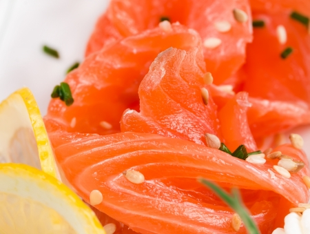 Sliced ​​salmon with sesame seeds and lemon photo