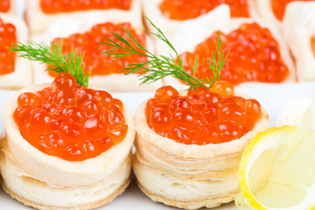 Tartlets with red caviar on a white plate with lemon photo