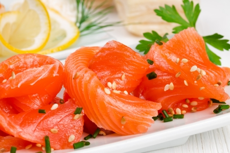 Sliced salmon with sesame seeds and lemon photo