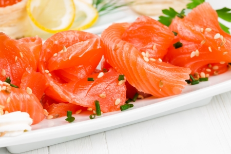 Sliced ​​salmon with sesame seeds and onions on a white plate photo