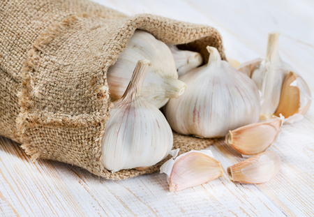 Garlic in a bag on an old wooden surface. Stock Photo - 22623049