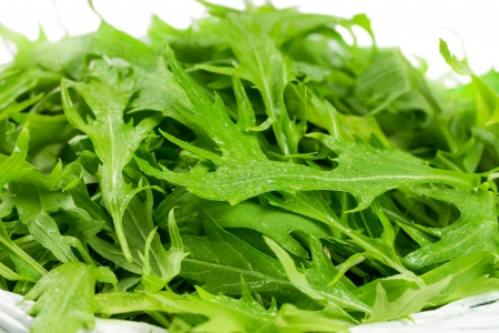 Arugula salad in a wicker basket isolated on white background photo